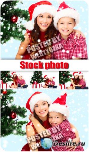 Женщина с ребенком у новогодней елки - сток фото